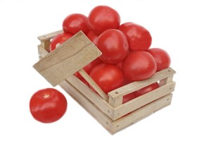 Many tomatoes in wooden box and price board